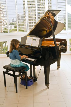 grand piano: little girl playing the grand piano