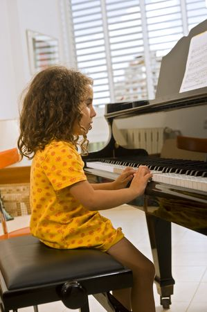 teaching music: little girl playing the grand piano
