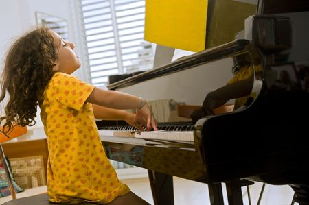 little girl playing the grand piano photo