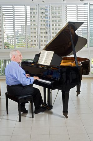 senior man playing on a grand piano at home Stock Photo - 3644037