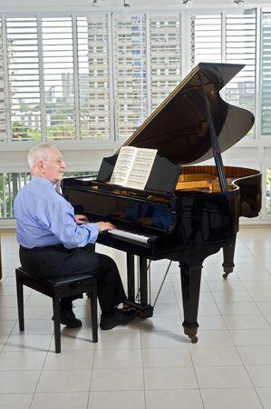 senior man playing on a grand piano at home photo