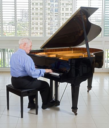 keyboard player: senior man playing on a grand piano at home