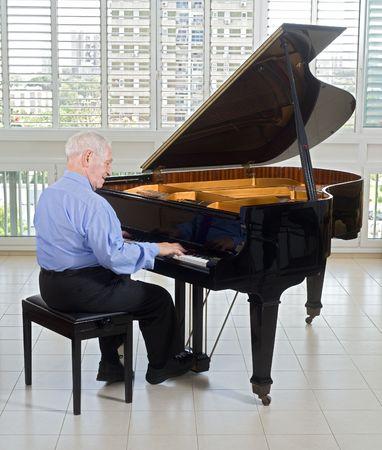 piano player: senior man playing on a grand piano at home