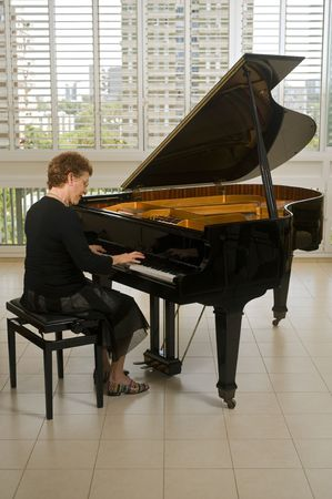 piano player: senior women pianist playing on a grand piano Stock Photo