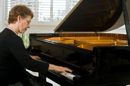 pianista: mujeres de edad pianista tocando en un piano de cola Foto de archivo