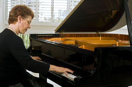 pianist: senior women pianist playing on a grand piano Stock Photo