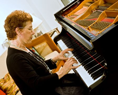 senior women pianist playing on a grand piano Stock Photo