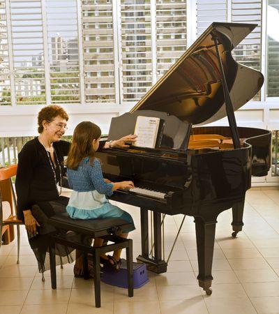 fortepian: starszy fortepian nauczyciel z młodą dziewczynę studenta Zdjęcie Seryjne