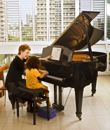 educadores: profesor superior de piano con el joven estudiante Foto de archivo