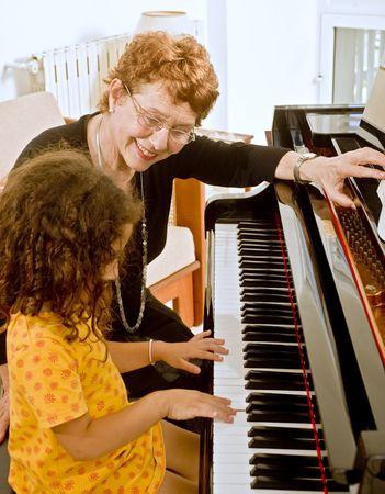 tocando el piano: profesor superior de piano con el joven estudiante Foto de archivo