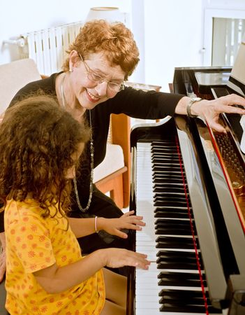 senior piano teacher with young girl student photo