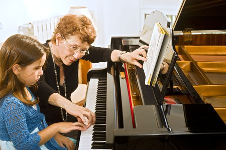 sled: senior piano teacher with young girl student Stock Photo