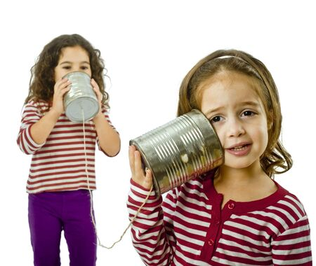 two girls talking on a tin phone isolated on white Stock Photo - 3755421