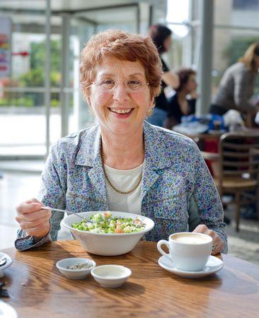 senior women: senior women having salad and coffee in a coffee shop