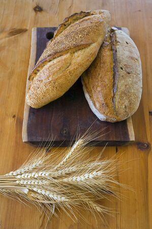 two loafs of sour dough bread with bundle of wheat Stock Photo - 3785150