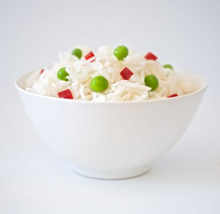 bowl of rice with peas an peppres on white