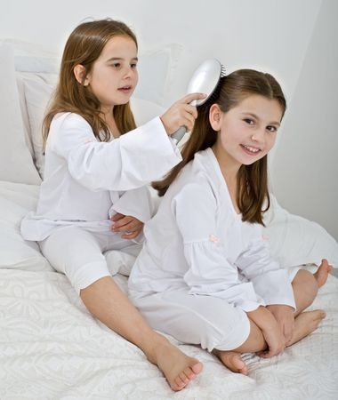 two young girl friends combing each other hair