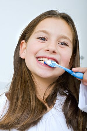 young girl brushing her teeth happily photo
