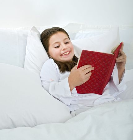 young girl lying in bed and reading a red book photo