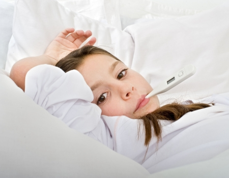 young girl lying in bed with a thermometer photo