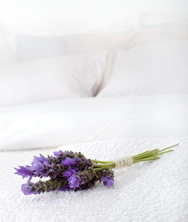 aroma de lavanda en una toalla blanca sobre una cama Foto de archivo