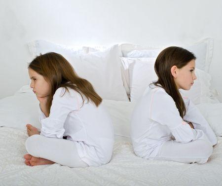 jealous: two little girls back to back in quarrel