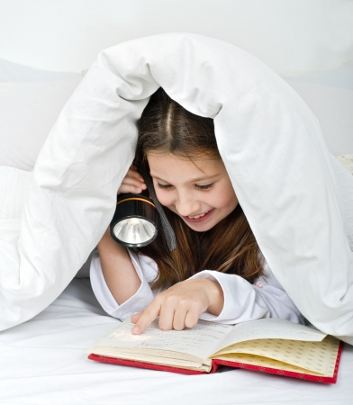 bedding indoors: girl reading under blanket with flashlight