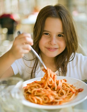 eating noodles: young girl eating spaghetti in restaurent