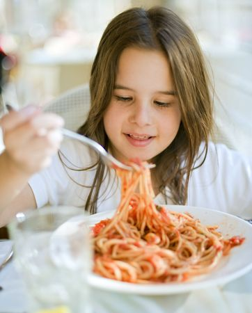 young girl eating spaghetti in restaurent photo