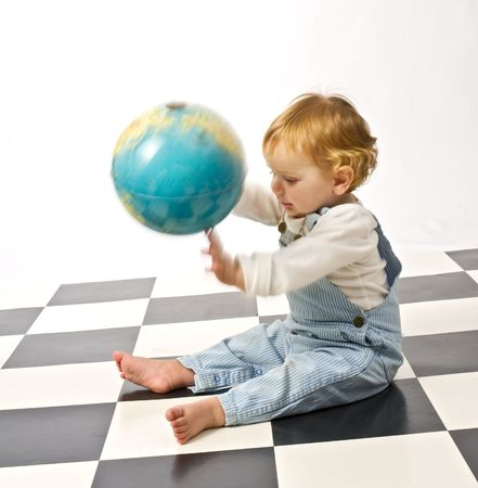 little boy playing with a globe on a checkered floor photo