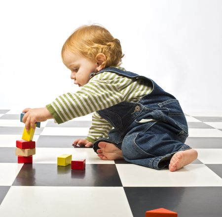 little boy playing with building blocks on a checkered floor photo