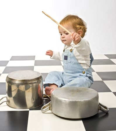 little boy druming playing with pots photo