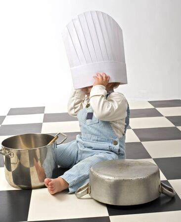 little boy druming playing with pots and chefs hat photo