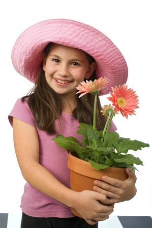 pink hat: young girl with a pink hat and pink daisies in a flowerpot