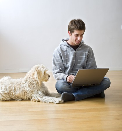 teenager with a laptop computer and his dog on a parquet floor