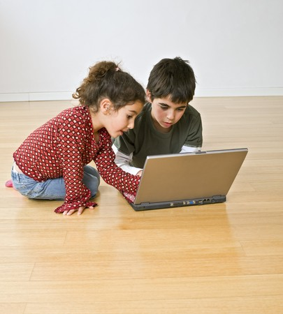two kids with laptop computer on the floor Stock Photo