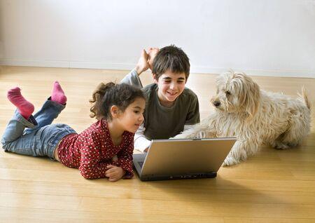 zwei Kinder und einen Hund mit Laptop-Computer auf den Boden