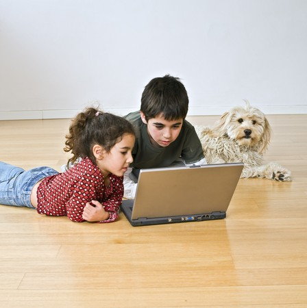 two kids and a dog with laptop computer on the floor Stock Photo - 3997798