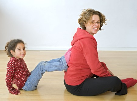 mother and child exercising together on floor photo