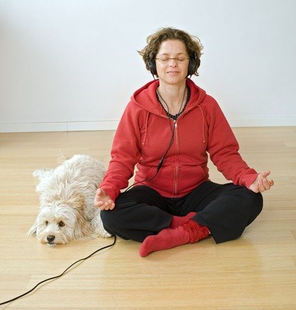 woman meditating with headphons and dog photo