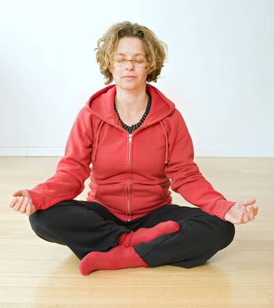 woman sitting on a parquet floor meditating photo
