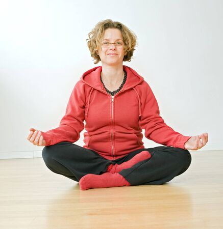 woman sitting on a parquet floor meditating Stock Photo - 3997793