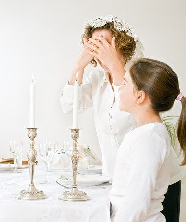 mother and daughter with shabbat candels photo