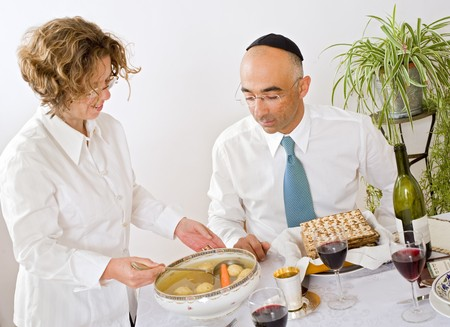 mother serving Kneidel soup at Passover family Seder Stock Photo