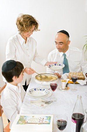 matzoth: mother serving Kneidel soup at Passover family Seder Stock Photo