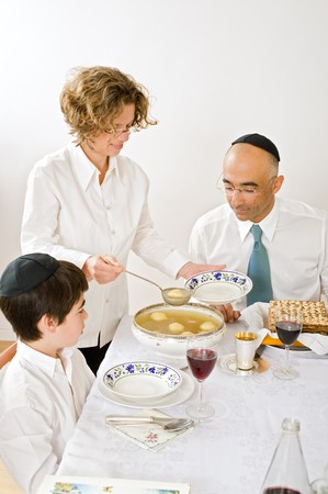 mother serving Kneidel soup at Passover family Seder Stock Photo - 4030023