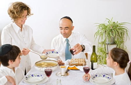 father mother son and daughter in seder celebrating passover photo