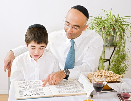 father and son celebrating passover reading the Hagada photo