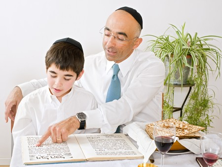 judaism: father and son celebrating passover reading the Hagada