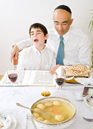 father and sun celebrating passover reading the Hagada photo